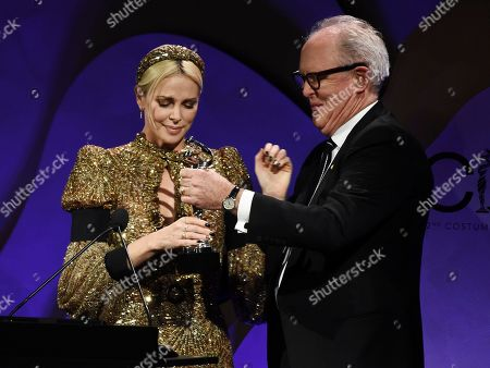 Charlize Theron, John Lithgow. Actress Charlize Theron, left, accepts the Spotlight Award from presenter John Lithgow during the 22nd Annual Costume Designers Guild Awards at the Beverly Hilton, in Beverly Hills, Calif
