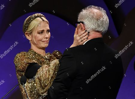 Charlize Theron, John Lithgow. Actress Charlize Theron accepts the Spotlight Award from presenter John Lithgow during the 22nd Annual Costume Designers Guild Awards at the Beverly Hilton, in Beverly Hills, Calif