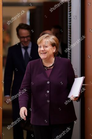 Stock Photo of German Chancellor Angela Merkel arrives for the weekly cabinet meeting of the German government at the chancellery in Berlin, . In the background left the President of Germany's Federal Bank Jens Weidmann