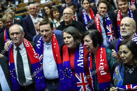British MEP's Richard Corbett, left, along with another British MEP's participate in a ceremony prior to the vote on the UK's withdrawal from the EU, the final legislative step in the Brexit proceedings, at the European Parliament in Brussels, . The U.K. is due to leave the EU on Friday, Jan. 31, 2020, the first nation in the bloc to do so
