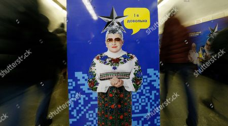 """People rush about their business past a poster depicting Ukrainian singer Verka Serduchka with text declaring """" I'm happy"""", at a city underground metro station in Kyiv, Ukraine"""
