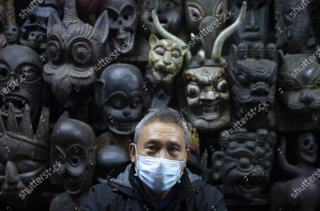 A vendor of traditional masks wears a facial mask at his shop in Thamel, a major tourist hub in Kathmandu, Nepal, 29 January 2020. Nepal's Health Ministry confirmed the first case of a coronavirus case in the country on 24 January 2020. Airports around the world are stepping up measures to stop the spreading of the novel coronavirus. Chinese authorities have urged people to stop travelling in and out of Wuhan, the city at the center of the new virus outbreak that has so far killed over 100 people and infected over thousands others, mostly in China.