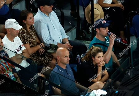 Mirka Federer, bottom right, sits with supporters as they watch her husband Roger in his semifinal against Serbia's Novak Djokovic at the Australian Open tennis championship in Melbourne, Australia