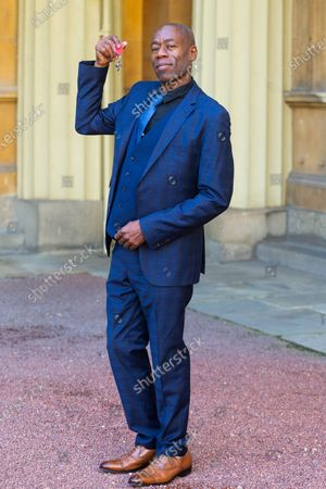 Andrew Roachford admires his MBE for services to music, following an investiture conducted by The Princess Royal at Buckingham Palace in London.