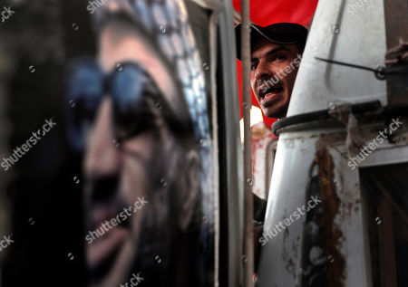 A Palestinian man stands next of a portrait of former Palestinian President Yasser Arafat, as he shouts slogans during a protest against the White House plan for ending the Israeli-Palestinian conflict, at Burj al-Barajneh refugee camp, south of Beirut, Lebanon, . At refugee camps across the country, Palestinians staged strikes, protests and sit-ins a day after U.S. President Donald trump revealed the long-awaited details of the plan, denouncing it as ridiculously lop-sided and saying it gives them no rights