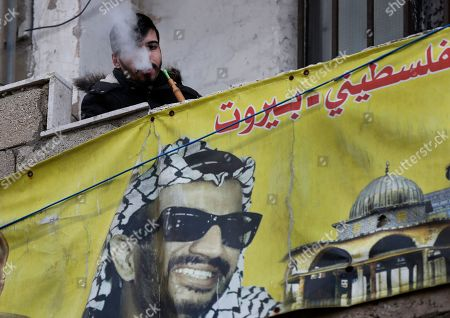 A Palestinian man smoke water pipe as he sits over a portrait of former Palestinian President Yasser Arafat, during a protest against the White House plan for ending the Israeli-Palestinian conflict, at Burj al-Barajneh refugee camp, south of Beirut, Lebanon