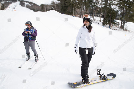 Democratic presidential candidate Rep. Tulsi Gabbard, D-Hawaii, right, speaks to supporters and staff as she prepares to snowboard at Cranmore Mountain Resort, in North Conway, N.H