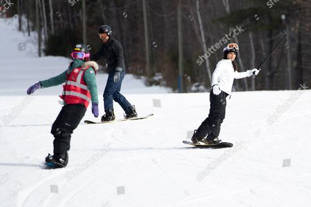 Democratic presidential candidate Rep. Tulsi Gabbard, D-Hawaii, right, snowboards with supporters and staff at Cranmore Mountain Resort, in North Conway, N.H