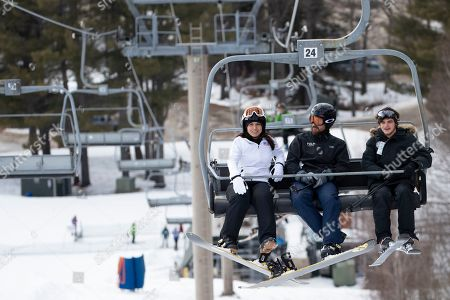 Democratic presidential candidate Rep. Tulsi Gabbard, D-Hawaii, left, ride a ski lift while snowboarding with supporters and staff at Cranmore Mountain Resort, in North Conway, N.H