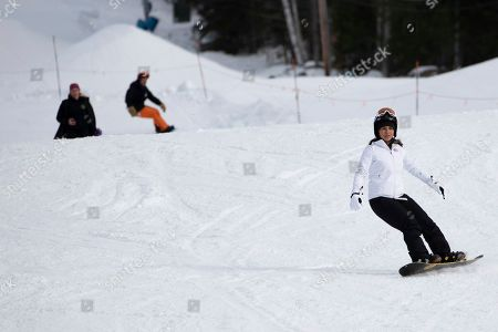 Stock Picture of Democratic presidential candidate Rep. Tulsi Gabbard, D-Hawaii, right, snowboards with supporters and staff at Cranmore Mountain Resort, in North Conway, N.H