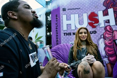In this Wednesday, Jan., 22, 2020 photo Lima Herrera, right, looks on as Anthony McPheeters takes a puff of marijuana from a bong during a visit to the Hush Supply booth at WeedCon Wonderland Expo in the Hollywood section of Los Angeles. It was a two day B2B networking & education expo promoting distributors, brands and farms