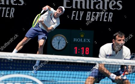Slovakia's Filip Polasek, left, serves as his partner Croatia's Ivan Dodig waits during their doubles semifinal against Australia's Max Purcell and Luke Saville at the Australian Open tennis championship in Melbourne, Australia