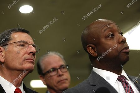 US Senator John Barrasso, a Republican from Wyoming and U.S. Senator Mike Braun, a Republican from Indiana and US Senator Tim Scott, a republican from South Carolina listen to a question from a reporter during a break from the impeachment trial at the Capitol