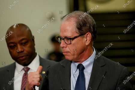 US Senator Tim Scott, a republican from South Carolina listens as Senator Mike Braun, a Republican from Indiana, talks to reporters during a break from the impeachment trial at the Capitol