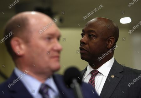US Senator Tim Scott, a republican from South Carolina listens as Christopher A. Coons, Junior US Senator from Delaware speak to reporters during a break from the impeachment trial at the Capitol