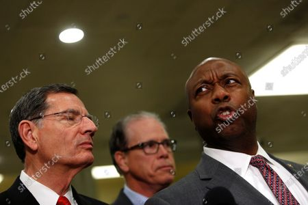 Stock Picture of US Senator John Barrasso, a Republican from Wyoming and U.S. Senator Mike Braun, a Republican from Indiana listen to US Senator Tim Scott, a republican from South Carolina speak to reporters during a break from the impeachment trial at the Capitol