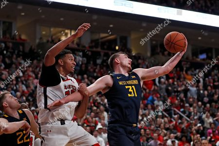 Logan Routt, TJ Holyfield. West Virginia's Logan Routt (31) rebounds the ball around Texas Tech's TJ Holyfield (22) during the second half of an NCAA college basketball game, in Lubbock, Texas