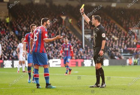 James Tomkins of Crystal Palace protests as he's shown a yellow card for a foul - referee Andy Madley