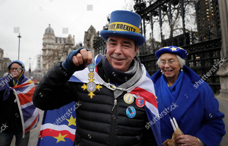 Anti-Brexit campaigner Steve Bray displays his 'OBR' 'Order of the Brexit Resistance' presented to him by a supporter, as he stands outside Parliament in London, . Although Britain formally leaves the European Union on Jan. 31, little will change until the end of the year. Britain will still adhere to the four freedoms of the tariff-free single market ? free movement of goods, services, capital and people