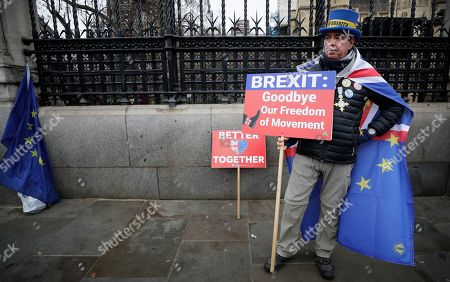 Anti-Brexit campaigner Steve Bray holds banners as he stands outside Parliament in London, . Although Britain formally leaves the European Union on Jan. 31, little will change until the end of the year. Britain will still adhere to the four freedoms of the tariff-free single market ? free movement of goods, services, capital and people