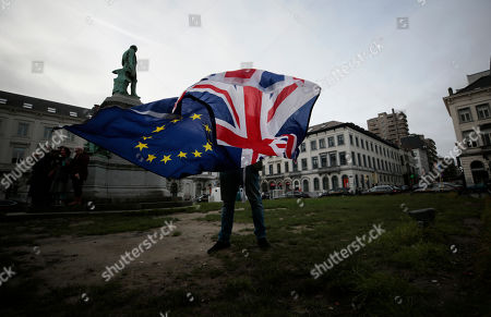 Stock Photo of Pro-EU supporter Peter Cook unfurls a Union and EU flag prior to a ceremony to celebrate British and EU friendship outside the European Parliament in Brussels, . The European Union grudgingly let go of the United Kingdom with a final vote Wednesday at the EU's parliament that ended the Brexit divorce battle and set the scene for tough trade negotiations in the year ahead