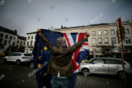 Pro-EU supporter Peter Cook holds up a Union and EU flag prior to a ceremony to celebrate British and EU friendship outside the European Parliament in Brussels, . The European Union grudgingly let go of the United Kingdom with a final vote Wednesday at the EU's parliament that ended the Brexit divorce battle and set the scene for tough trade negotiations in the year ahead