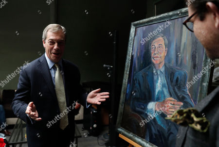 Stock Image of Brexit Party leader Nigel Farage, left, speaks to a small gathering after he unveiled a portrait of himself entitled Mr Brexit with the aid of the artist Dan Llywelyn Hall, in London, . The painting is to be sold in aid of a charity that looks after military veterans