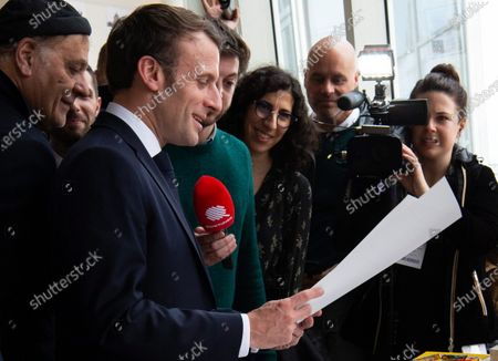 French President Emmanuel Macron (2-L) speaks to journalists next to Serbian director and designer Enki Bilal (L) before a visit to the exhibition 'In the head of Pierre Christin' during Angouleme Comics Festival 2020, at  Angouleme, Southwestern France, 30 January 2020.