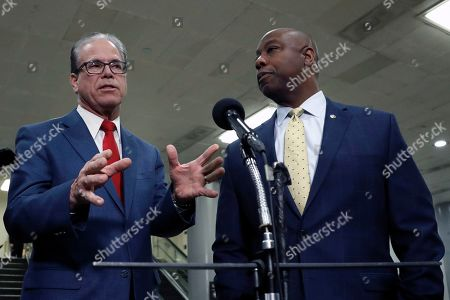 Sen. Mike Braun, R-Ind., left, talks to reporters as Sen. Tim Scott, R-S.C., listens in the basement of the U.S. Capitol in Washington, during the impeachment trial of President Donald Trump on charges of abuse of power and obstruction of Congress