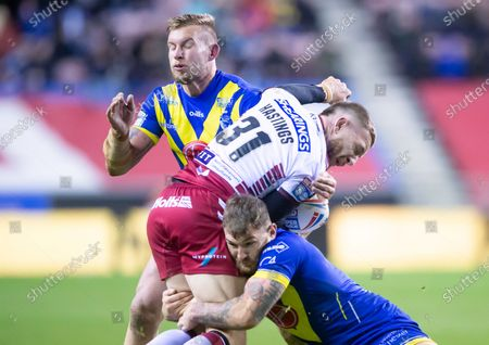 Wigan's Jackson Hastings is tackled by Warrington's Mike Cooper & Daryl Clark.