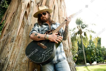 "Billy Ray Cyrus poses for a portrait with an Ovation guitar presented to him by Neil Diamond in 1992, at his home in Los Angeles on. The Kentucky-born singer won his first Grammy this year for his collaboration with rapper Lil Nas X on ""Old Town Road."" He's releasing a three-song EP on Friday, ""The Singing Hills Sessions: Vol. 1"