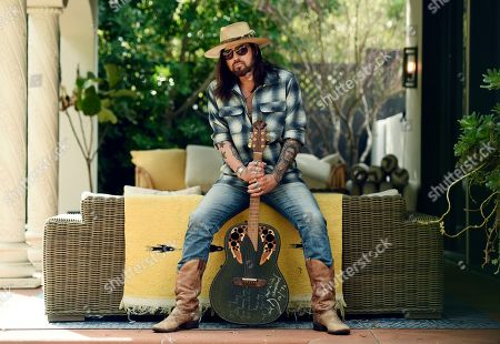 "Stock Photo of Billy Ray Cyrus poses for a portrait with an Ovation guitar presented to him by Neil Diamond in 1992, at his home in Los Angeles on. The Kentucky-born singer won his first Grammy this year for his collaboration with rapper Lil Nas X on ""Old Town Road."" He's releasing a three-song EP on Friday, ""The Singing Hills Sessions: Vol. 1"