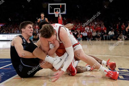 Villanova's Collin Gillespi, left, and St. John's David Caraher fights for control of the ball during the first half of an NCAA college basketball game, in New York