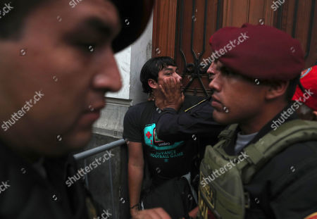Stock Image of A supporter of opposition leader Keiko Fujimori, the daughter of Peru's former President Alberto Fujimori, is held back by police officers outside a courtroom in Lima, Peru, . A Peruvian judge ordered 15 months of preventive detention for Keiko Fujimori while she is investigated for alleged money laundering related to the Brazilian construction company Odebrecht