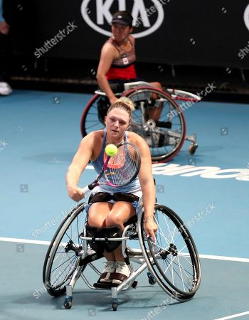 Britain's Jordanne Whiley plays a backhand return as her partner Japan's Yui Kamiji watches against Dieke De Groot and Aniek Van Koot of the Netherlands in the women's wheelchair doubles final at the Australian Open tennis championship in Melbourne, Australia