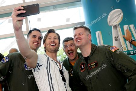 Glen Powell ; Miles Teller ; Monica Barbaro. Top Gun: Maverick' actor Glen Powell, center, takea a selfie with the U.S. Navy pilots that will be performing a flyover at the Super Bowl, in Miami Beach, Fla