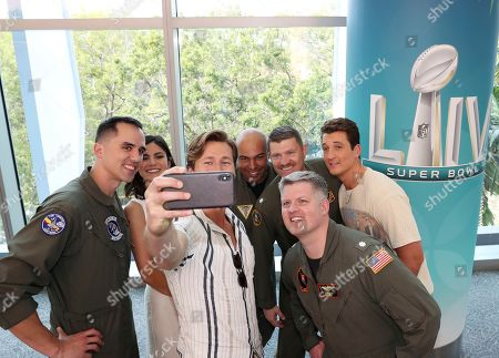Glen Powell ; Miles Teller ; Monica Barbaro. Top Gun: Maverick' actors, Glen Powell, center, Miles Teller, right and Monica Barbaro take a selfie with the U.S. Navy pilots that will be performing a flyover at the Super Bowl, in Miami Beach, Fla