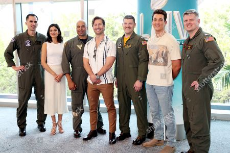 Glen Powell ; Miles Teller ; Monica Barbaro. Top Gun: Maverick' actors, Monica Barbaro, left, Glen Powell, center, Miles Teller, pose with the U.S. Navy pilots that will perform a flyover at the Super Bowl, in Miami Beach, Fla