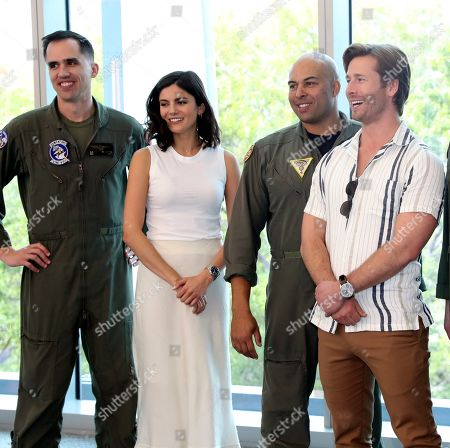 """Glen Powell ; Miles Teller ; Monica Barbaro. Top Gun: Maverick"""" actors, Glen Powell, center, Miles Teller, right and Monica Barbaro pose for photos with U.S. Navy pilots that will be performing a flyover at Super Bowl LIV, in Miami Beach, Fla"""