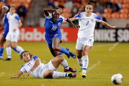Haiti forward Nerilia Mondesir (10) is tackled by Costa Rica forward Raquel Rodriguez (11) while Costa Rica forward Melissa Herrera (7) watches during the second half of a CONCACAF women's Olympic qualifying soccer match, in Houston