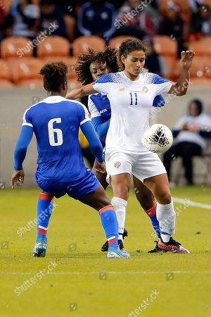 Costa Rica forward Raquel Rodriguez (11) brings down the ball between Haiti midfielders Melchie Dumonay (6) and Danielle Etienne, back, during the second half of a CONCACAF women's Olympic qualifying soccer match, in Houston