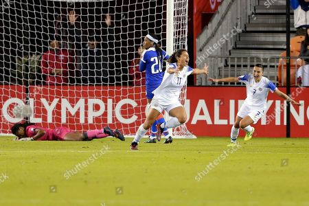 Haiti goalkeeper Kerly Theus, left, lies on the field next to midfielder Kethna Louis (20) as Costa Rica forward Raquel Rodriguez (11) and forward Melissa Herrera (7) celebrate a goal by Rodriguez during the second half of a CONCACAF women's Olympic qualifying soccer match, in Houston