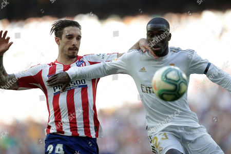 Atletico Madrid's Sime Vrsaljko, left, challenges for the ball with Real Madrid's Ferland Mendy during a Spanish La Liga soccer match between Real Madrid and Atletico Madrid at the Santiago Bernabeu stadium in Madrid