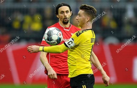 Union's Neven Subotic, left, and Dortmund's Marco Reus, right, challenge for the ball during the German Bundesliga soccer match between Borussia Dortmund and Union Berlin in Dortmund, Germany