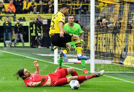 Union's Neven Subotic, down, and Dortmund's Achraf Hakimi, up, challenge for the ball during the German Bundesliga soccer match between Borussia Dortmund and Union Berlin in Dortmund, Germany