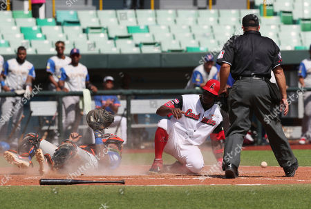Venezuela's Rene Reyes, center, slides safely onto home plate and scores a run against Colombia's pitcher Andury Acevedo during the Caribbean Series baseball game in San Juan, Puerto Rico