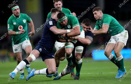 Ireland vs Scotland. Scotland's Huw Jones and Rory Sutherland tackle CJ Stander of Ireland