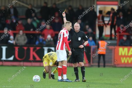 Luke Varney gets a yellow card after a tackle on Jordan Cranston during the EFL Sky Bet League 2 match between Cheltenham Town and Morecambe at Jonny Rocks Stadium, Cheltenham