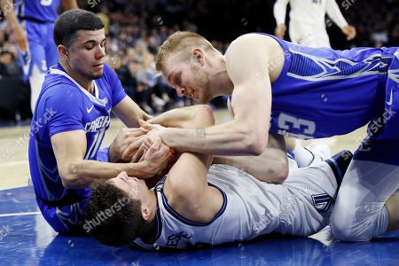 Collin Gillespie, Marcus Zegarowski, Kelvin Jones. Villanova's Collin Gillespie, center, tries to hang on to a loose ball against Creighton's Marcus Zegarowski, left, and Kelvin Jones during the first half of an NCAA college basketball game, in Philadelphia