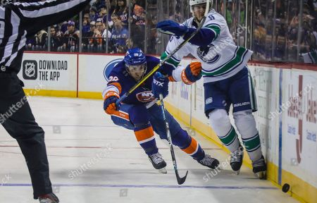 New York Islanders left wing Michael Dal Colle, left, and Vancouver Canucks center J.T. Miller (9) chase after the puck during an NHL hockey game., at Barclays Arena in New York